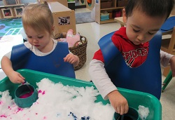 toddlers painting with snow